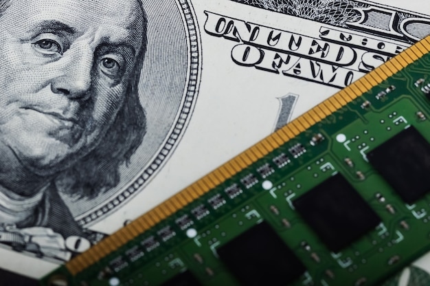 Computer board and one hundred dollars bill closeup.