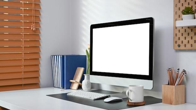 コンピュータ、コーヒーカップ、本、観葉植物、ホームオフィスのインテリアの鉛筆ホルダー。