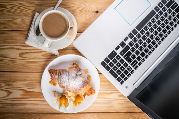 Computer, cup coffee and croissant on brown wood table