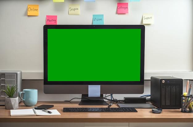 Рабочий стол компьютера с канцелярскими принадлежностями и устройством, показывающим зеленый экран во время видеоконференции