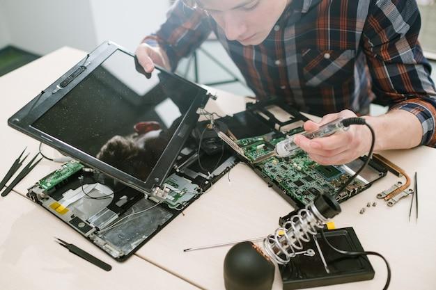 분해 된 노트북을 고정하는 컴퓨터 엔지니어. 과학 기술 전자 설계 개발
