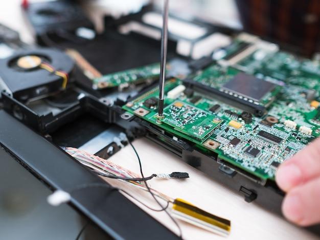 분해된 노트북을 수리하는 컴퓨터 엔지니어. 과학 기술 전자 설계 개발