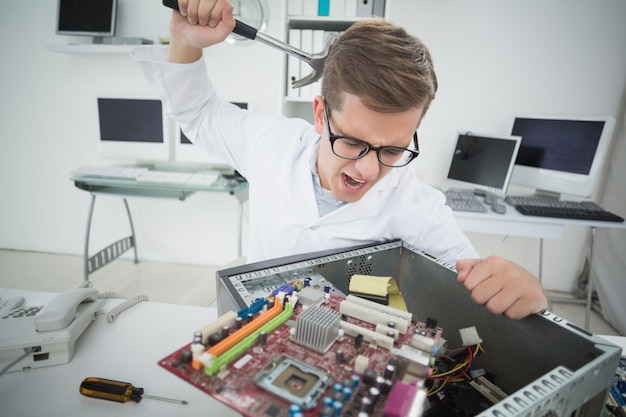 Computer engineer holding hammer over broken console