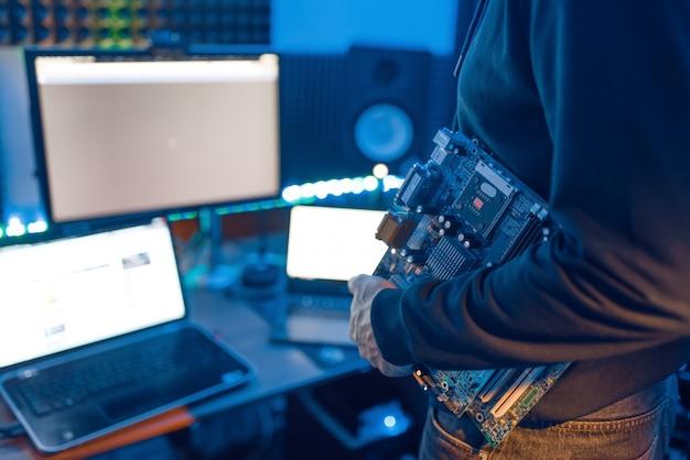 コンピューターエンジニアは、pcのマザーボードを保持しています。