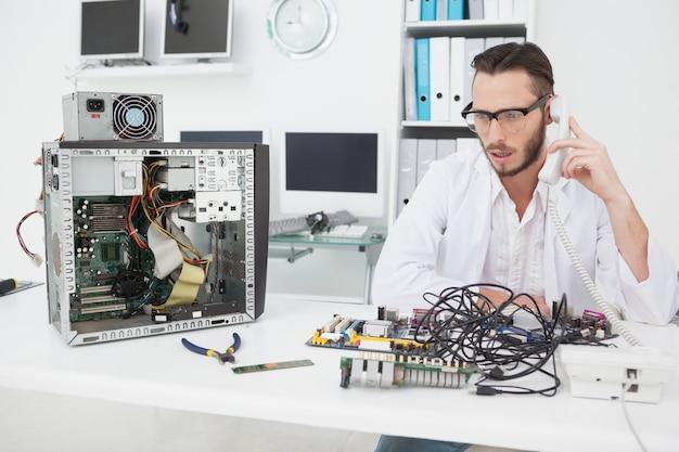 깨진 된 장치를보고 전화를하는 컴퓨터 엔지니어