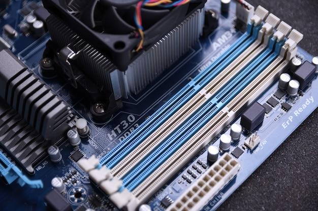 Вентилятор компьютера на материнской плате и электронных компонентах памяти процессора и графического процессора и различных разъемов для видеокарты крупным планом