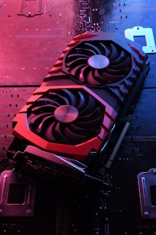 Computer game graphics card, videocard with two coolers on circuit board  close-up. with red-blue lighting.