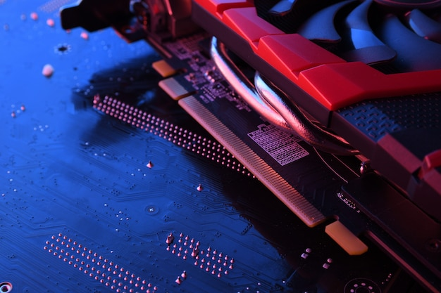 Computer game graphics card, videocard with two coolers on circuit board, motherboard. close-up. with red-blue lighting
