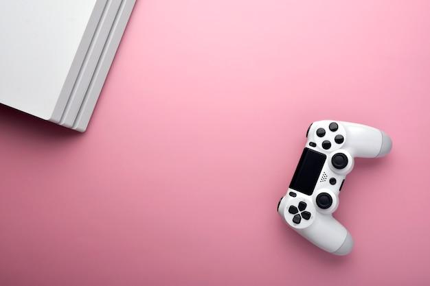 Игрок в компьютерные игры. игровая концепция белый джойстик и конор компьютера на розовом фоне.