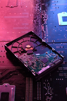 Computer hard disk drives hdd, ssd on circuit board, motherboard. close-up. with red-blue lighting