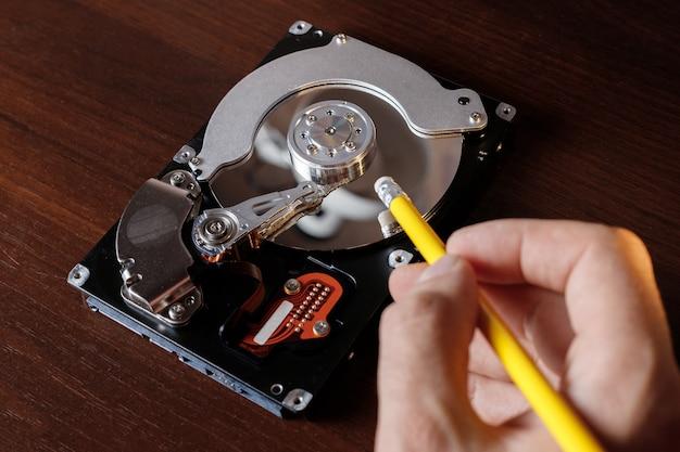 Жесткий диск компьютера и карандаш с ластиком крупным планом