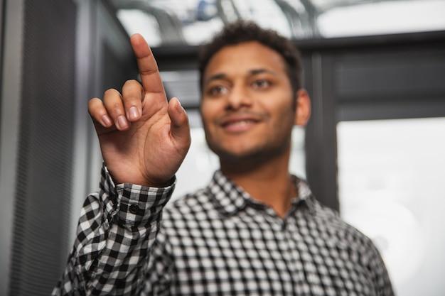 コンピューターハードウェア。サーバールームに立って手を上げる陽気なit技術者のローアングル