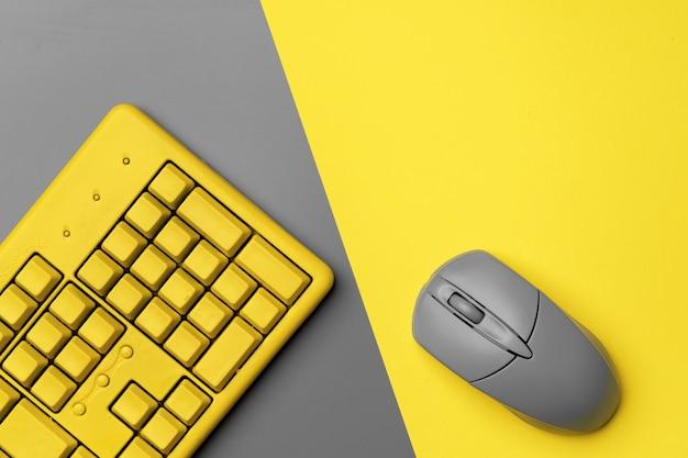 Компьютерная клавиатура и мышь в желто-серых тонах сверху