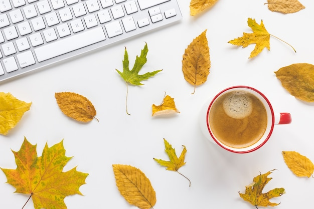 Computer keyboard cup of espresso and yellow fall leaves on white background autumn mood
