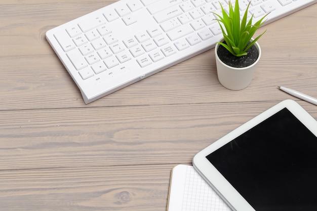 Computer keyboard and digital tablet close up on wooden desk
