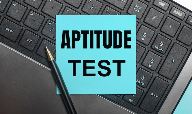 The computer keyboard has a pen and a blue sticker with the text aptitude test. flat lay.