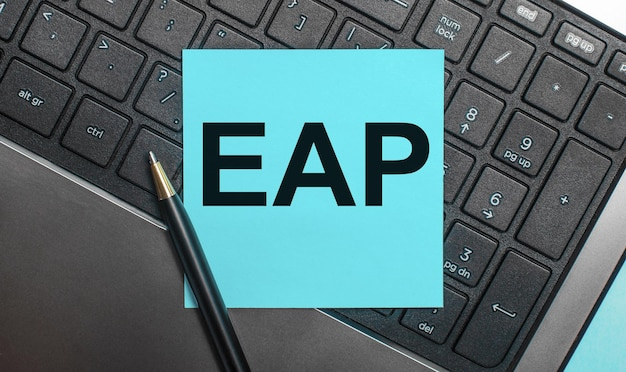 The computer keyboard has a pen and a blue sticker with the text eap employee assistance program. flat lay.