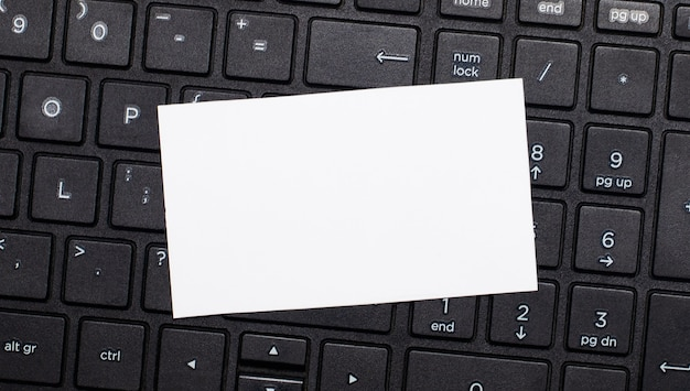 The computer keyboard has a white blank card for inserting text. template. top view with copy space