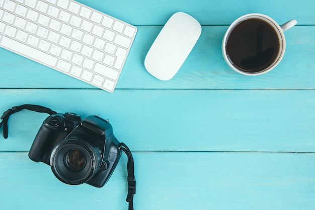 Computer keyboard and mouse, cup of coffee and camera on blue wooden background with copy space. freelance concept, earnings in the photo