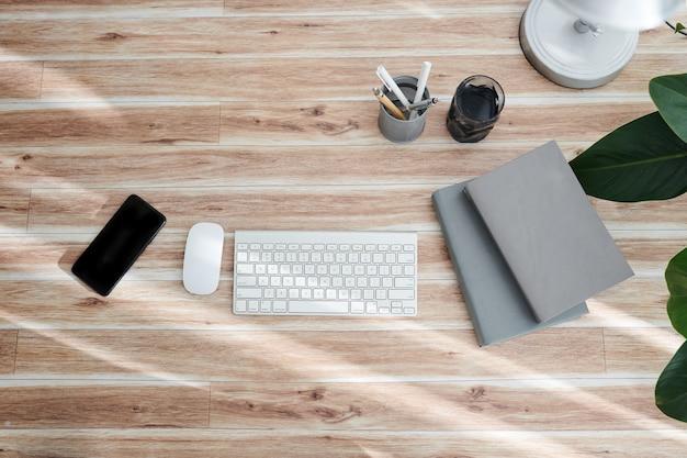 Компьютерная клавиатура, мышь, смартфон и книги на офисном столе, вид сверху
