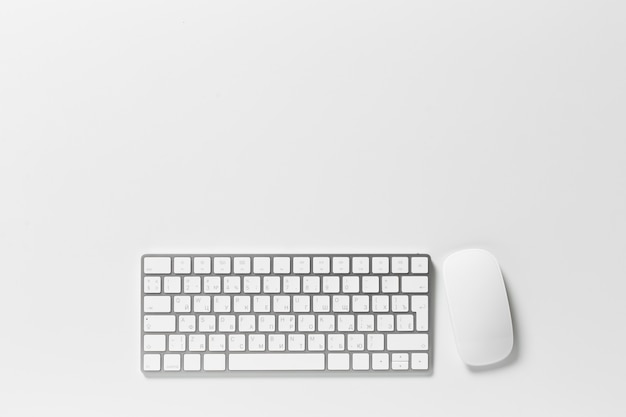 Computer keyboard and mouse on top of white desktop