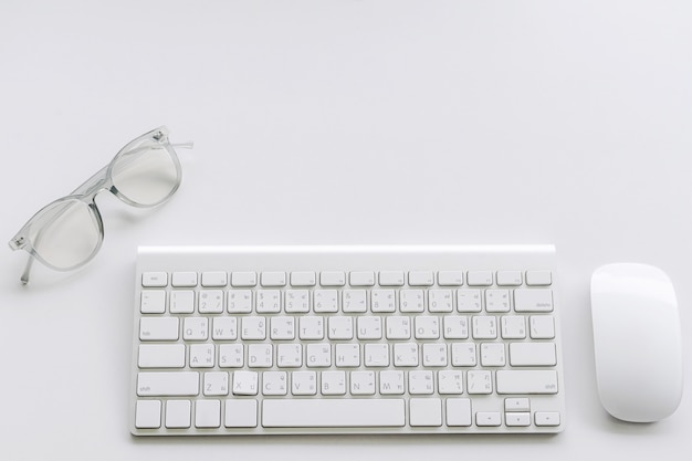 Computer keyboard and mouse with glasses on white background