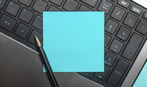 On a computer keyboard, a pen and a blue sticker with space to insert text or illustrations. flat lay.