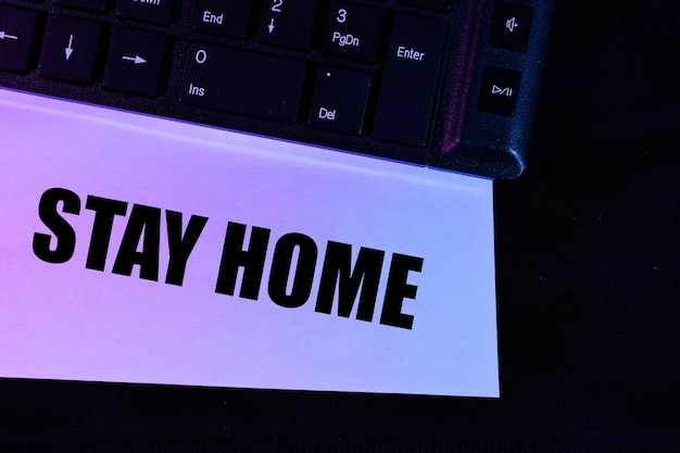 Computer keyboard in pink and blue with the words stay home
