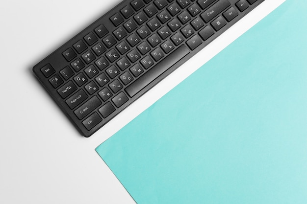Computer keyboard on a turquoise paper