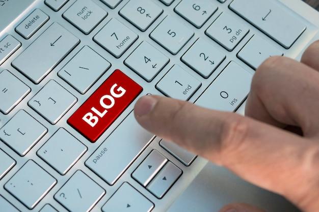 テキストブログ付きのコンピューターのキーボード。ブロガーは、現代のラップトップの灰色の銀色のキーボードのカラーボタンを押します。碑文のボタンをクローズアップ。ブログを作成する