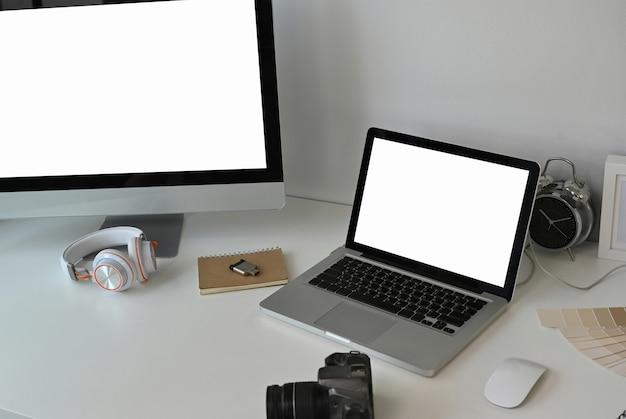 白いテーブルの上のコンピューター、ラップトップ、およびカメラ