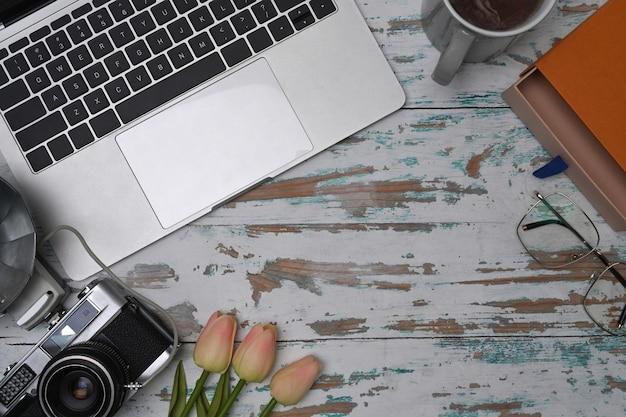Компьтер-книжка, камера, кофейная чашка и тетрадь на деревянном столе.