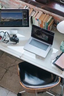 A computer, a laptop, and a camera on a desk