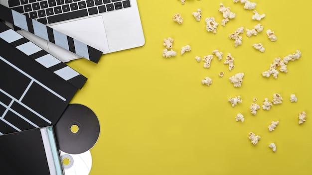 Ноутбук, вагонка и попкорн на желтом фоне.