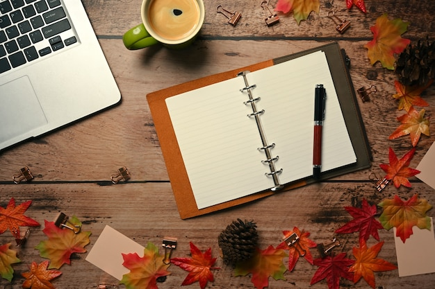 Computer laptop, empty notebook, coffee cup and autumn maple leaves on wooden table.