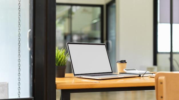 コンピューターのラップトップは、背景にぼやけたオフィスのインテリアと画像空白画面の概念をモックアップ
