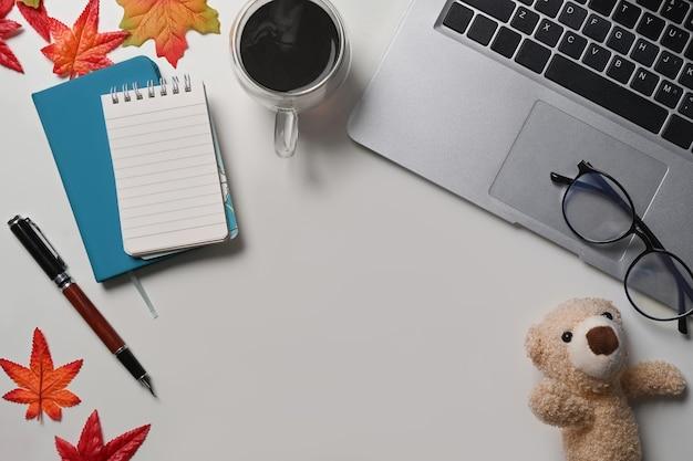 흰색 테이블에 컴퓨터 노트북, 메모장, 커피 컵, 안경, 단풍나무 잎.