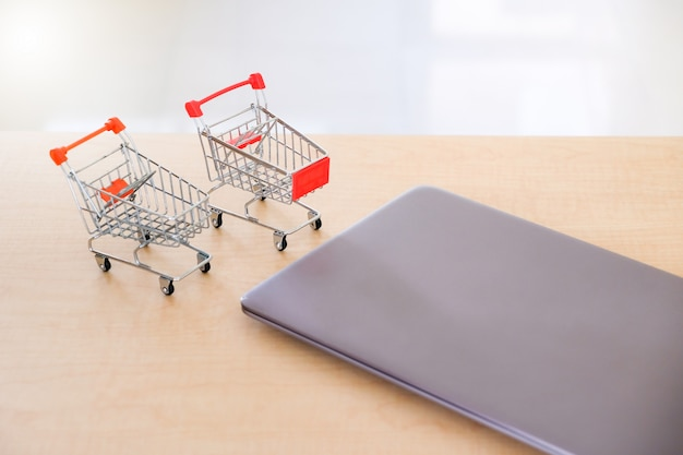 Computer laptop and small shopping cart on wooden table in modern office