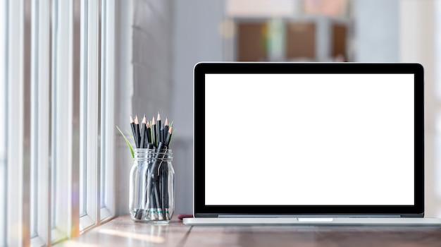 現代的な部屋のテーブルに空白の画面を持つコンピューターのラップトップ。グラフィックデザインのための空白の画面を持つモックアップノートパソコン。