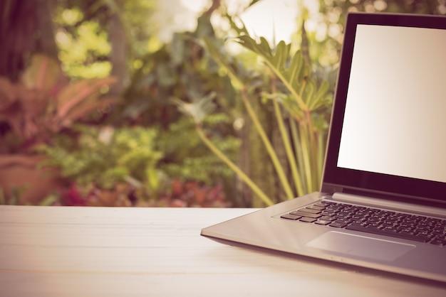 녹색 정원 자연 배경 빈 흰색 화면 나무 테이블 컴퓨터 노트북