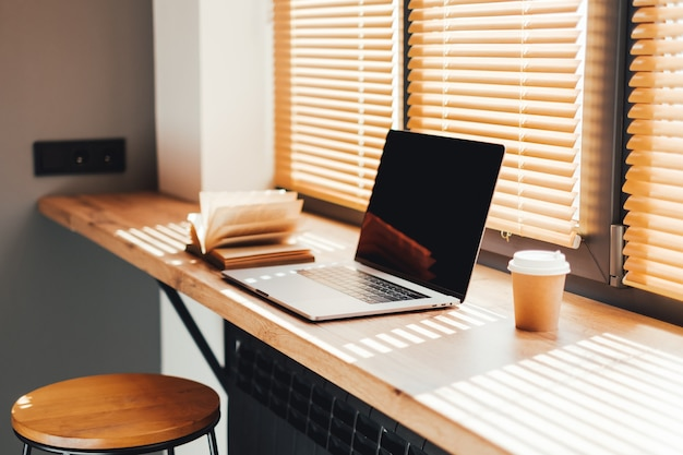 Computer laptop with coffee cup and open book on the modern wooden table on the kitchen