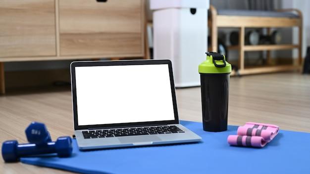 Компьютер-ноутбук с пустым экраном, бутылкой воды и гантелями на синем коврике.