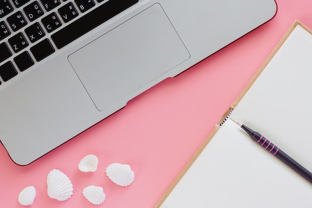 Computer laptop with a pen, an opened notebook and sea shells on pink color background