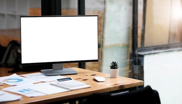 흰색 빈 화면이 있는 컴퓨터 노트북은 커피 컵, 책 더미, 화분, 편안한 거실 창문 위에 연필로 둘러싸인 나무 작업용 책상을 배경으로 합니다.