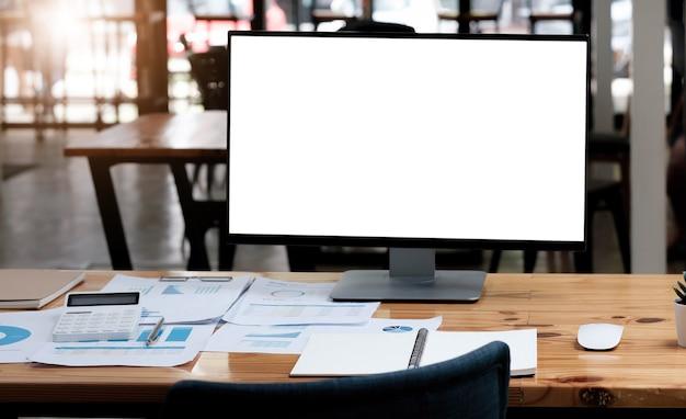 흰색 빈 화면이 있는 컴퓨터 노트북은 커피 컵, 책 더미, 화분, 연필로 둘러싸인 나무 작업용 책상 위에 놓여 있습니다.
