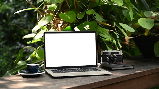 Computer laptop with white screen, coffee cup and camera on wooden table in the green garden.