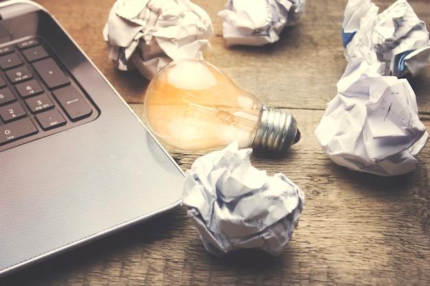 コンピューターのラプター、電球、そして多くのしわが寄った紙
