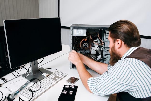 Компьютерный мастер разбирает процессор с помощью специальных инструментов. рабочее место ремонтника с набором винтов и монитора на столе. концепция ремонта пк
