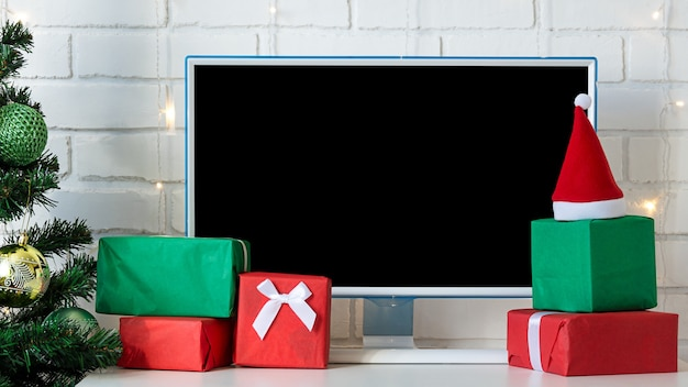Computer monitor and green and red gift boxes next to the christmas tree.
