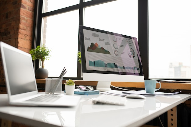 Компьютерный монитор с графической информацией на экране, ноутбук, кружка и другие принадлежности на столе у окна офиса